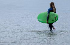 Une jeune apprentie surfeuse se met à l'eau pour un cours de surf